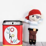 Amigurumi Pirate Leaning On A Small, Tin, Money Box With Yo, Ho Ho On The Side || thecrochetspace.com