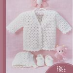 Lacy Baby Crochet Set. Crafted in white. Cadigan on a hanger with booties and bonnet underneath || thecrochetspace.com