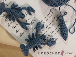 Little Leo Crochet Lobster. Two complete little lobsters, and one more body just started. Crafted in Blue yarn and laid out on an open white page in a book with writing on it || thecrochetspace.com