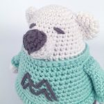 Master Malcolm Crochet Bear.Side view of top of bear. Sweater in Turquoise with large grey M on the front of sweater || thecrochetspace.com