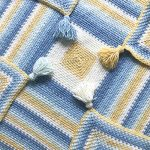 Mossy Square Crochet Blanket with tassels at each corner. Yarn is self striping blue, yellow and white || thecrochetspace.com