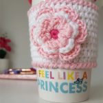 Mug Hugger Crocheted Coffee Cozy. Mug cozy in white with pink edging with accent flower in same pink and white added || thecrochetspace.com