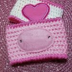 Mug Hugger Crocheted Coffee Cozy. Two mug cozy's. One in white with bright pink edging and a heart accent and the other crafted in two shades of pink and an added accent label || thecrochetspace.com