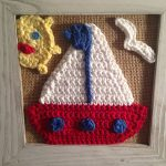 Nicely Nautical Crochet Accents. Close up of hanging frame with ship, half-sun and sea gull. Crafted in red, white and blue || thecrochetspace.com