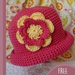 Pretty-Pixie Crochet Hat. Crafted in a red/pink with accent flower. Flower material behind hat || thecrochetspace.com