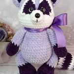 Plush Crochet Velvet Raccoon. Crafted in violet and lilac velvet yarn with large lilac ribbon at neck || thecrochetspace.com