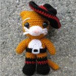 Puss In Crochet Boots. Front view. Tilted sombrero on head, buckle belt and black boots || thecrochetspace.com