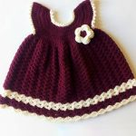 Sara Crochet Baby Dress. Front view of burgundy dress with cream edging and accent flower. Angel ing sleeves || thecrochetspace.com