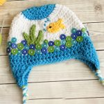 Sea Life Crochet Hat. Hat laid out on table. Hat crafted in blues and white with yellow fish and green grass || thecrochetspace.com