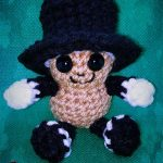 Seasonal Amigurumi Peanut Bestie. Against a teal colored background. Cafted in beige and black || thecrochetspace.com
