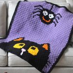 Seasonal Crochet C2C Blanket. Black and Purple Halloween blanket, with cats face and hanging spider || thecrochetspace.com