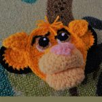 Simba Lion Crochet Applique. Amigurumi lips, large eyes and a tuft of orange yarn at the front for hair || thecrochetspace.com