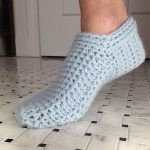 Simple Spa Crochet Slippers. Image of one ,male foot arched in a slipper. Light grey and closely fitted. No cuff || thecrochetspace.com