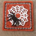 Spider Crochet Granny Square. Terracotta square with white spiders web and black spider || thecrochetspace.com