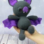 Spooky Halloween Bat. Bat laying in a person's hand. Bat crafted in black and purple || thecrochetspace.com