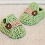Stylish Crochet Baby Moccasins crafted in pale green yarn with beige bar across front and accent button || thecrochetspace.com