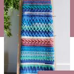 Summer Blues Crochet Afghan. Afghan folded and hanging on a rustic ladder || thecrochetspace.com