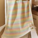 Sunlight Crochet Baby Blanket. Image of blanket draped over a chair in multi light colors || thecrochetspace.com