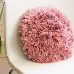 Super Shaggy Crochet Pillow. Sitting on a white chair    thecrochetspace.com