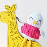 Sweetie Sue Crochet Bird One bird with long, thin legs and wearing a pink sweater sitting on a yellow cardboard giraffe || thecrochetspace.com