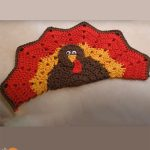 Turkey Crocheted Place Mat. Sitting turkey shape crafted as a place mat in seasonal colors || thecrochetspace.com