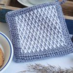 Typical Tunisian Crochet Potholder. Border of plain grey and then an inserted inlay of white contrasting diamonds || thecrochetspace.com