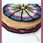 Wheel Spoke Crochet Coaster. Single coaster in process of being crafted. Sitting on top of a plain cork inner    thecrochetspace.com